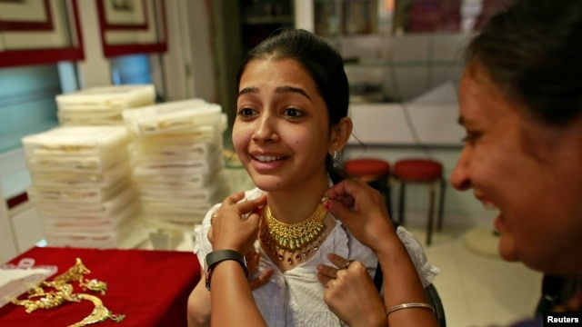 Girl tries on gold necklace inside jewelry showroom in Mumbai, Apr. 16, 2013.