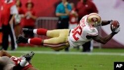 Kendall Hunter, de los 49ers de San Francisco, se lanza para anotar en el triunfo sobre los Bucaneros, 33 a 14.