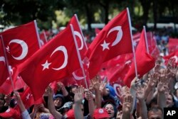 FILE - Pro-government demonstrators wave Turkish flags as they protest against the attempted coup in Istanbul, Turkey, July 19, 2016.
