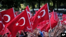FILE - Pro-government demonstrators wave Turkish flags as they rally against the attempted coup in Istanbul, Turkey, July 19, 2016. The Turkish government accelerated its crackdown on alleged plotters of the failed coup against President Recep Tayyip Erdogan.