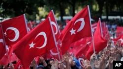 2016年7月19日,支持土耳其政府的群众在伊斯坦布尔挥舞国旗,抗议政变行动。土耳其政府加快清洗与政变有牵连的人。