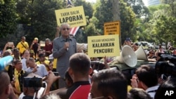 "Malaysia's opposition coalition prime ministerial candidate Mahathir Mohamad speaks against a controversial proposal to redraw electoral boundaries outside near the Parliament House in Kuala Lumpur, Malaysia March 28, 2018. The sign (front R) reads: ""Go o"
