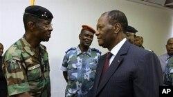 Rais wa Ivory Coast, Alassane Ouattara(R) akipeana mkono na Jenerali Philippe Mangou, kwenye hoteli ya Golf mjini Abidjan.