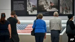 Visitors view the display for the American flag, left, that firefighters hoisted at ground zero in the hours after the 9/11 terror attacks, Sept. 8, 2016, at the Sept. 11 museum in New York.