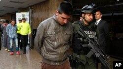 """Polisi mengawal Edgar Murillo, alias Payaso (depan, tengah) yang ditahan bersama tiga pria lainnya atas pembunuhan agen khusus polisi James """"Terry"""" Watson di Bogota, Kolombia. (Foto: Dok)"""