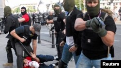 Plain clothes police officers arrest a soccer fan during clashes before the Poland and Russia Group A Euro 2012 soccer match in Warsaw, June 12, 2012.