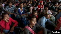Cambodian workers wait for their documents to be processed at the Aranyaprathet police station as they prepare to move back to Cambodia in Sa Kaew June 15, 2014. Due to shortage of employment back home, many Cambodian workers try to find jobs overseas.