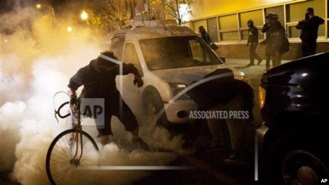 晚上10点过后,抗议者试图向防暴警察扔回催泪瓦斯罐。2015年4月28日,星期二,巴尔的摩,弗雷迪·格雷的葬礼后,周一发生骚乱,宵禁开始生效。(美联社照片)