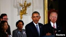 លោកប្រធានាធិបតី បារ៉ាក់ អូបាម៉ា និងអនុប្រធានាធិបតី Joe Biden ព្រមទាំងសមាជិកគ្រួសារជនរងគ្រោះដោយសារអំពើហិង្សាដោយកាំភ្លើង នៅក្នុងសុន្ទរកថាអំពីការកាត់បន្ថយអំពើហិង្សាដោយកាំភ្លើងនៅបន្ទប់ខាងកើតនៃសេតវិមាន ក្នុងរដ្ឋធានីវ៉ាស៊ីនតោន នៅថ្ងៃទី៥ ខែមករា ឆ្នាំ២០១៥។