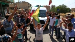 Supporters of Kurdish forces line the road as the convoy carrying the body of U.S. citizen Keith Broomfield, killed fighting militants of the Islamic State group in Kobani, passes through Suruc on the Turkey-Syria border, June 11, 2015.