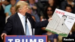 FILE - U.S. Republican presidential candidate Donald Trump holds a sign supporting his plan to build a wall between the United States and Mexico that he borrowed from a member of the audience at his campaign rally in Fayetteville, North Carolina, March 9, 2016.