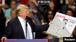 FILE - Donald Trump, then a candidate for the U.S. presidency, holds a sign supporting his plan to build a wall between the United States and Mexico that he borrowed from a member of the audience at his campaign rally in Fayetteville, North Carolina, March 9, 2016.