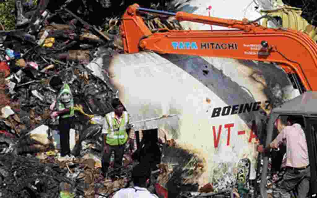 """Officials of Air India and the Airports Authority of India work at the plane crash site of the Air India Express Boeing 737-800 and searching for the """"black box"""" data recorder in Mangalore, 24 May 2010"""