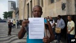 Jose Augusto memperlihatkan resumenya saat mengantri untuk mencari pekerjaan di Kementerian Tenaga Kerja Brazil di Rio De Janeiro, 31 Mei 2017.