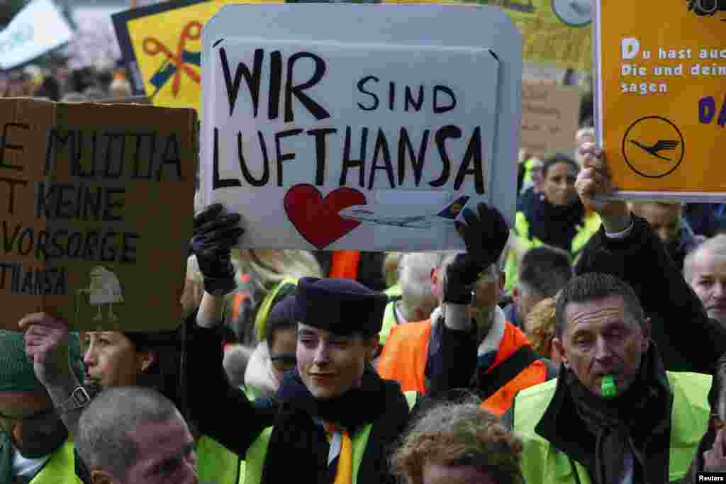 A Lufthansa employee holds up a placard reading 'we are Lufthansa' during a strike by cabin crew union at Frankfurt airport, Germany. Lufthansa has promised a return to normal flight schedules on Saturday. The week-long strike was expected to ground another 941 flights on Friday.