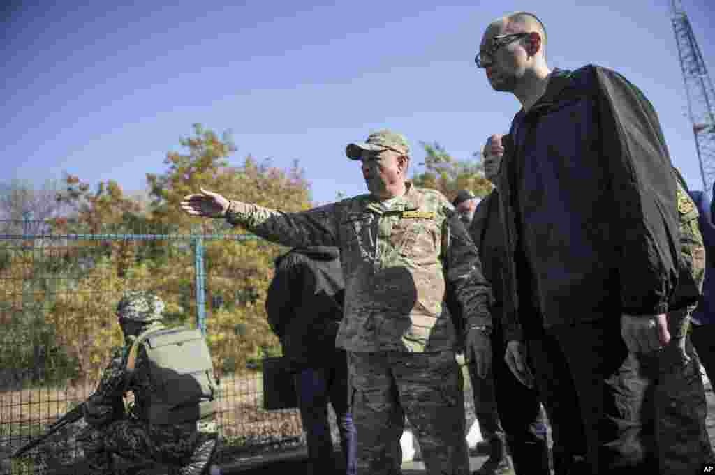 Ukrainian Prime Minister Arseniy Yatsenyuk, right, inspects part of Ukraine's eastern border with Russia close to Kharkiv, Ukraine, Oct. 15, 2014.