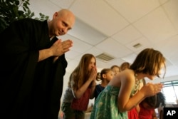 In this Sunday, June 19, 2011 photo, Rev. Jay Rinsen Weik bows with children after lighting an incense candle at the Toledo Zen Center in Holland, Ohio. The center has created a Sunday school and other programs to be especially welcoming to families.