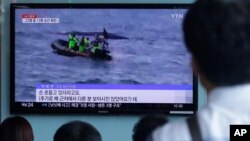 People watch a TV news program showing South Korean Coast Guard officers search for missing passengers after a fishing boat capsized in the water off north of the resort island of Jeju, at Seoul Railway Station in Seoul, Sept. 6, 2015