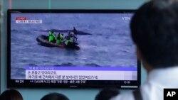 Orang-orang menonton berita penjaga pantai Korea Selatan mencari penumpang yang hilang setelah sebuah kapal nelayan tenggelam di pulau resor Jeju, di stasiun kereta api Seoul di Seoul, Korea Selatan, Minggu, 6 September 2015