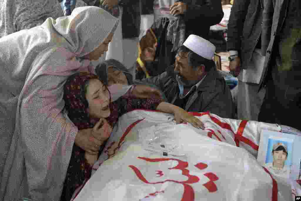 Seorang perempuan Pakistan dihibur oleh kerabatnya sambil menangisi jenazah kakaknya Mohammed Ali, yang tewas dalam pemboman hari Sabtu, di Quetta, Pakistan.