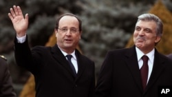 French President François Hollande walks with his Turkish counterpart Abdullah Gul during a welcome ceremony at the Cankaya Palace in Ankara, Turkey, Jan. 27, 2014.