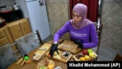 Fatima Ali prepares cheese-plate takeaway at her home kitchen in Baghdad, Iraq, Saturday, Nov. 28, 2020. (AP Photo/Khalid Mohammed)
