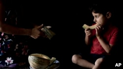Ardawan, 4, eats melon on the kitchen floor of an orphanage for Yazidi children in Sheikhan, Iraq. Aug. 22, 2108.