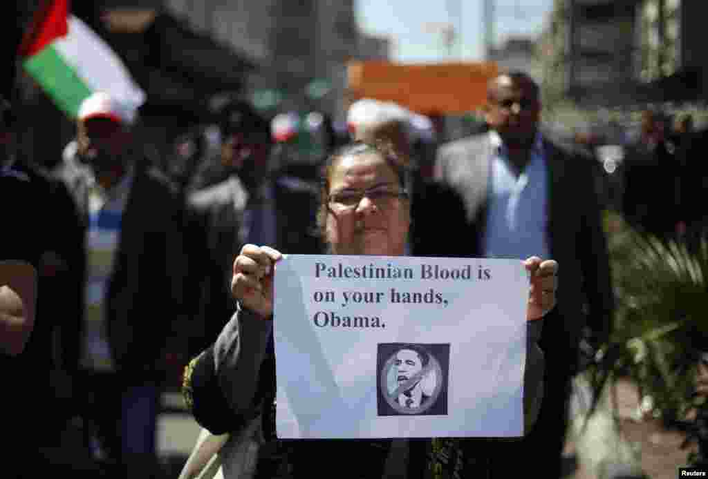 A Palestinian woman holds a sign during a protest against the visit of U.S. President Barack Obama, in Gaza City, March 20, 2013.