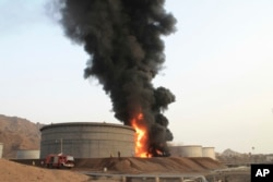 Firefighters work to extinguish a fire following rocket attacks by Shiite rebels known as Houthis at storage tanks of an oil refinery in the port city of Aden, Yemen, July 14, 2015.