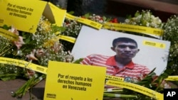 """FILE - Photo of a Venezuela citizen is seen in front of Venezuela's embassy building during a protest by the human rights organization Amnesty International in Lima, Peru, April 12, 2018. The signs on the ground read in Spanish """"Respcet human rights in Venezuela."""""""