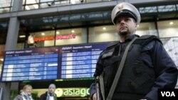 Seorang polisi berjaga-jaga menggunakan rompi anti-peluru di sebuah stasiun kereta di Berlin.