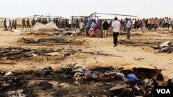 Pengungsi berkumpul dekat tenda-tenda yang hangus terbakar di kamp Coucha di Tunisia timur dekat perbatasan dengan Libya.