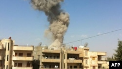 A handout picture released by the Syrian Arab News Agency (SANA) allegedly shows smoke rising as the state TV said a suicide car bomb rocked the Kurdish city of Qamishli, September 30, 2012.