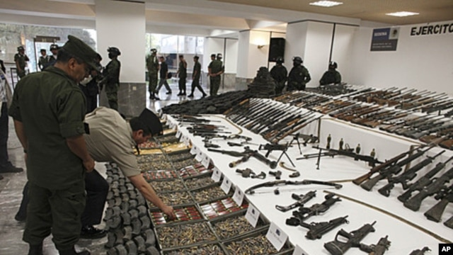 Soldiers review a weapons cache that includes 154 rifles and shotguns and over 92,000 rounds of ammunition during a media presentation, in Mexico City, Mexico, June 3, 2011