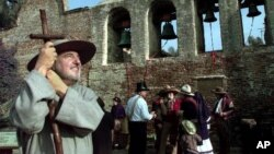 John Mione, playing Father Serra, looks skyward for swallows following the ringing of the bells in March 17 at the Mission San Juan Capistrano