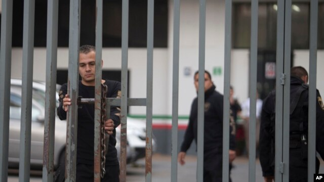 A security agent closes a gate outside the federal building housing the offices of the national immigration service, where Ethan Couch was seen departing in an immigration van shortly after, in Guadalajara, Mexico, Wednesday, Dec. 30, 2015.