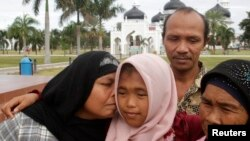 Jamaliah (L) kisses her daughter Raudhatul Jannah, 14, as the girl's father Septi Rangkuti and grandmother Sarwani look on following prayers at Baiturrahman mosque in Banda Aceh, Aug. 8, 2014.