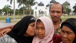 Jamaliah (L) kisses her daughter Raudhatul Jannah, 14, as the girl's father Septi Rangkuti and grandmother Sarwani look on following prayers at Baiturrahman mosque in Banda Aceh, Aug. 8, 2014.