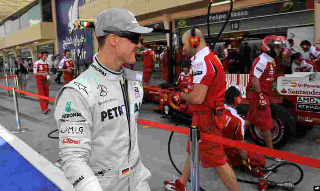Michael Schumacher looks to a Ferrari car as he walks through the pit lane before the first practice session at the Formula One Bahrain International Circuit in Sakhir, March 12, 2010.