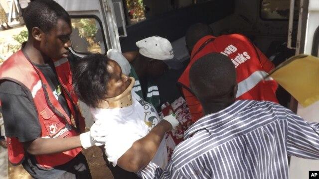 A woman injured in a grenade attack at the Utawala Inter-denominational church is helped into ambulance in Garissa, northern Kenya, November 4, 2012.