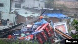 Cư dân thu nhặt các vật dụng còn sót lại từ đóng đổ nát của nhà cửa sau trận bão Nari tại Đà Nẵng.