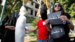 FILE - In this Thursday, April 1, 2010 file photo, activists from a civil organization reenact an execution scene in front of the Saudi Arabia Embassy in Beirut, Lebanon, as they protest a possible beheading of a Lebanese man accused of witchcraft in Saudi Arabia.