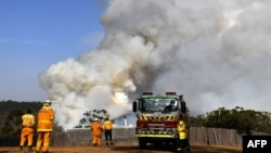 Firefighters work as smoke rises from a bushfire in Penrose, in Australia's New South Wales state on January 10, 2020. - High temperatures and strong winds were expected to fan massive bushfires blazing across southeastern Australia on January 10,…