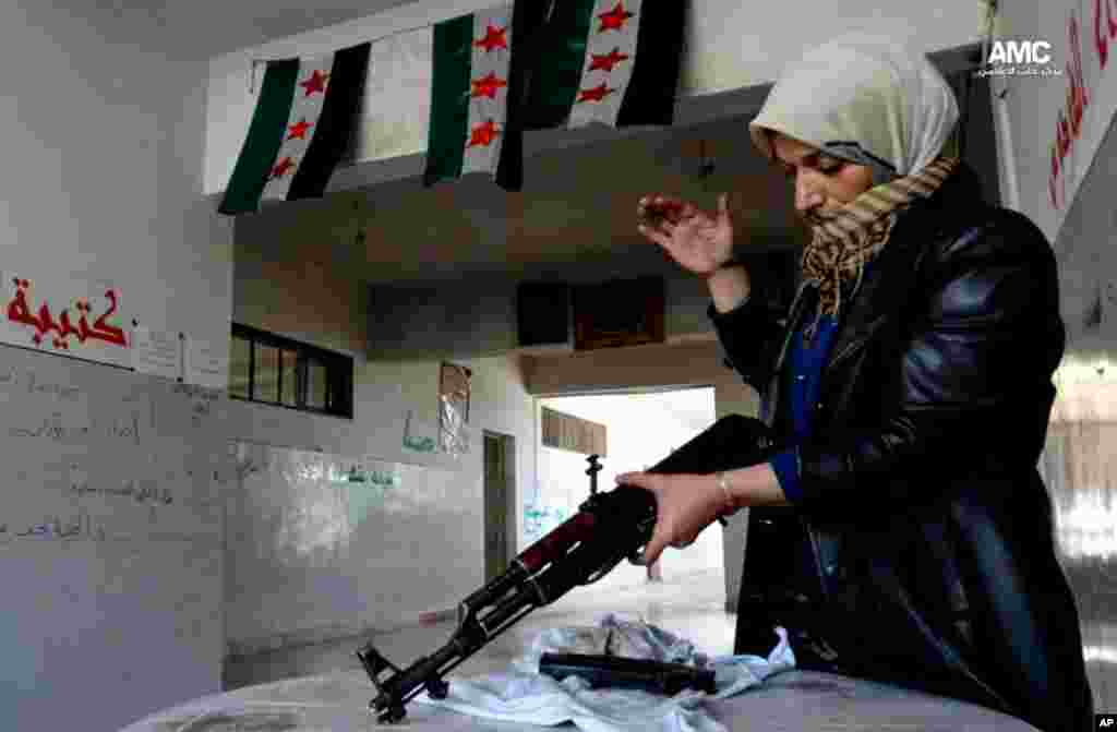This image provided by Aleppo Media Center AMC shows the mother of a Syrian rebel cleaning a rifle, in Aleppo, May 14, 2013.