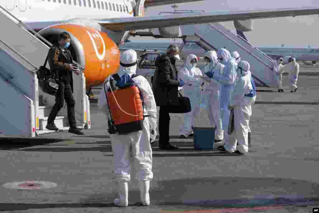 یک تیم پزشکی در فرودگاه بینالمللی در آلماتی، قزاقستان که مسافران هواپیمایی که از اوکراین آمده را برای احتمال داشتن علایم کرونا مورد آزمایش قرار میدهد.