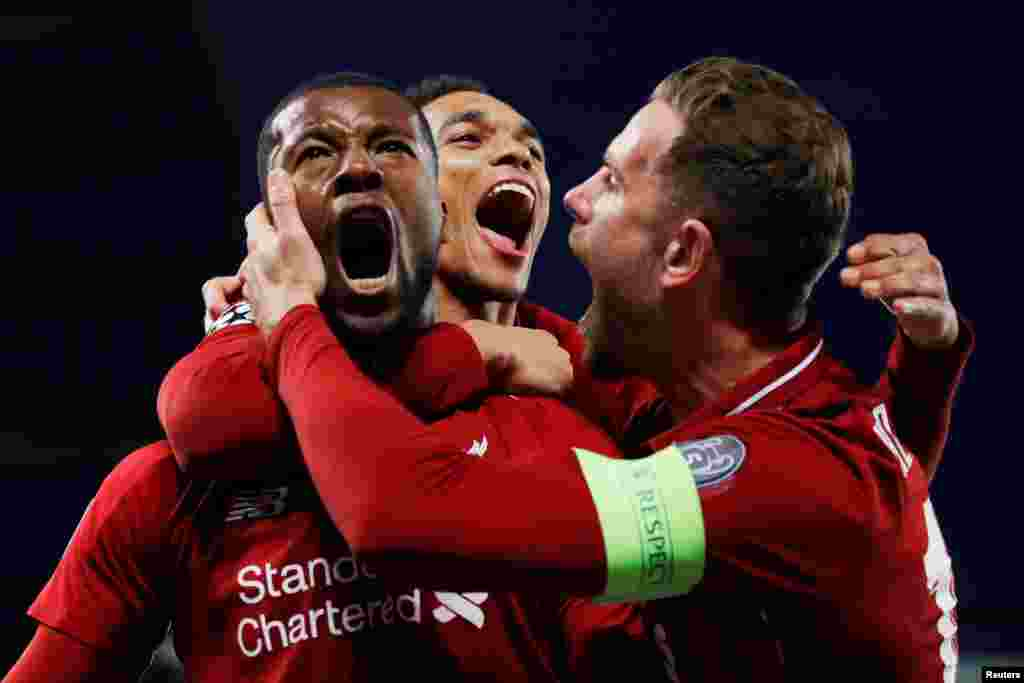 Liverpool's Georginio Wijnaldum celebrates scoring the team's third goal against Barcelona, with Jordan Henderson and Trent Alexander-Arnold, during the Champions League Semi Final Second Leg in Liverpool, Britain, May 7, 2019.