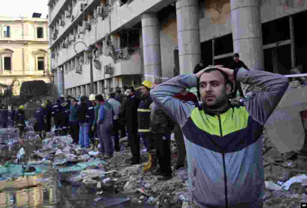 A man stands in rubble after an explosion at the Egyptian police headquarters in downtown Cairo. Three bombings hit high-profile areas around the city on Friday, including a suicide car bomber who struck the police headquarters.
