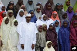 FILE - Nigeria President, Muhammadu Buhari (C), poses for a photograph with recently freed School girls from the Government Girls Science and Technical College Dapchi, by at the Presidential palace in Abuja, Nigeria, March 23, 2018.