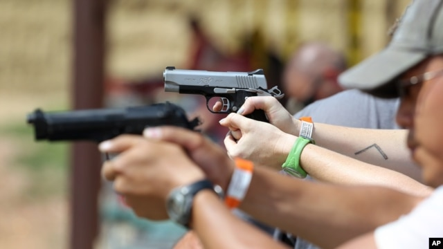 FILE - Shooters practice with pistols at a gun range near Colorado Springs, Colo.