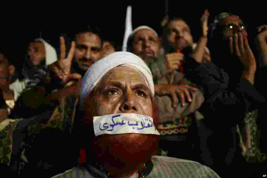 "A supporter of Egypt's ousted President Mohamed Morsi covers his mouth with tape. The Arabic writing reads: ""Military Coup,"" as others chant slogans against Egyptian Defense Minister Gen. Abdel Fattah el-Sissi at Rabaa al-Adawiya mosque, Cairo, Egypt."